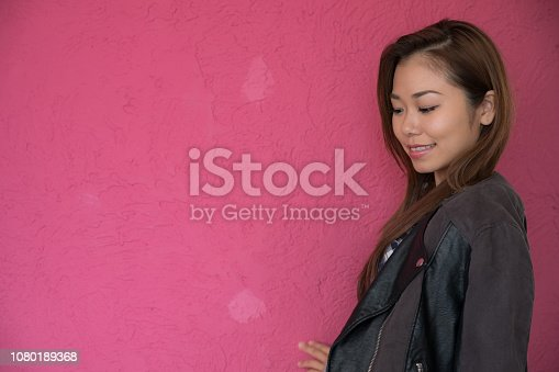 867955978 istock photo A woman posing in front of a pink wall. 1080189368
