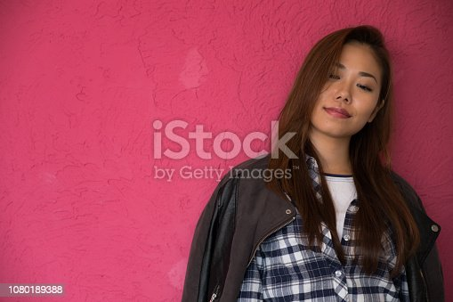 istock A woman posing in front of a pink wall. 1080189388
