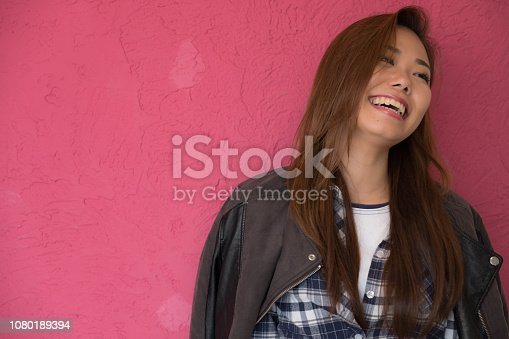 istock A woman posing in front of a pink wall. 1080189394