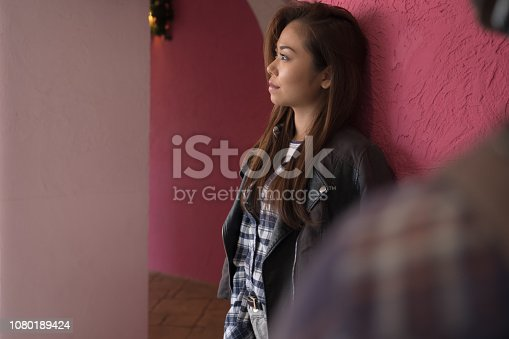istock A woman posing in front of a pink wall. 1080189424