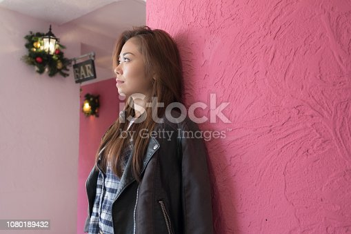 istock A woman posing in front of a pink wall. 1080189432