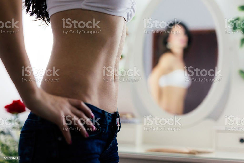 Woman posing in front of the mirror stock photo