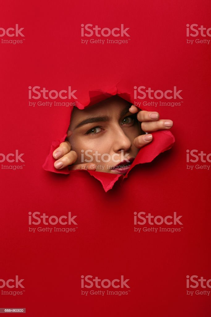 Young woman looking at camera while tearing red cardboard with hands.