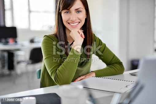 Attractive smiling brunette dressed casual holding hand on chin and sitting in modern office.