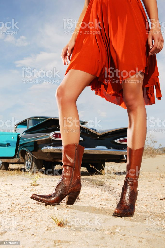 Woman posing in orange dress and boots beside classic car royalty-free stock photo