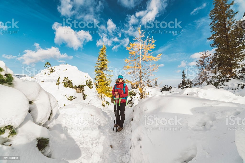 Woman posing in the middle of mountains after a snowfall stock photo