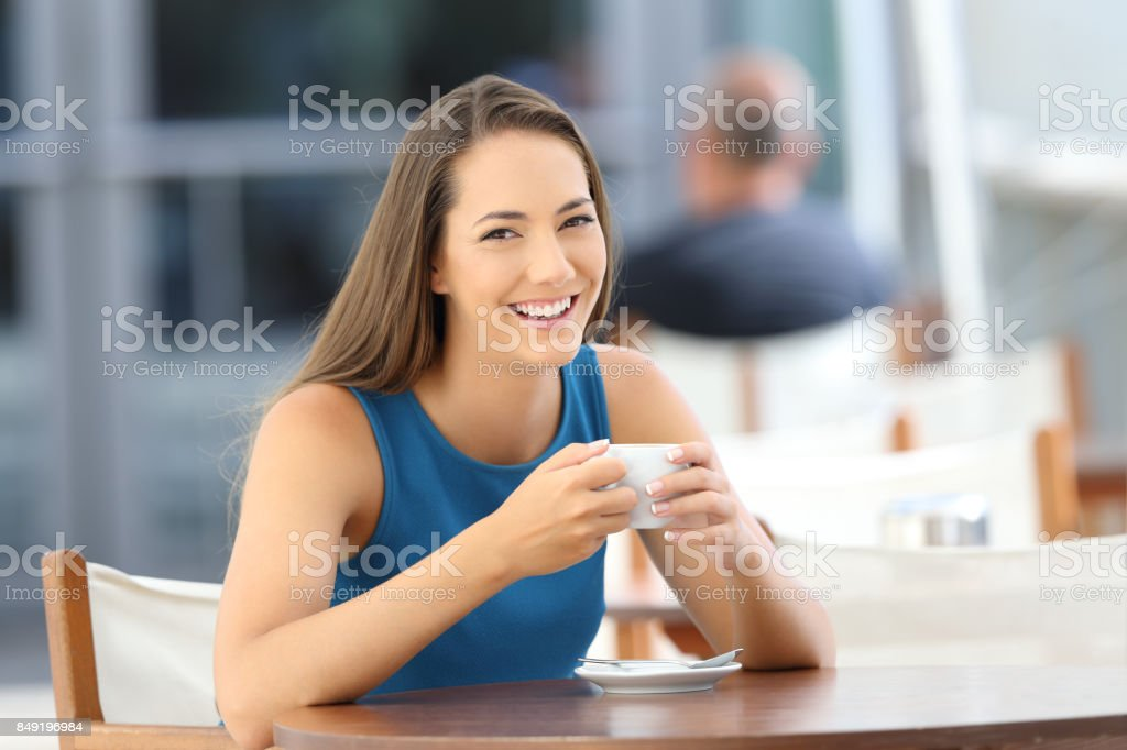 Woman posing looking at you in a coffee shop stock photo