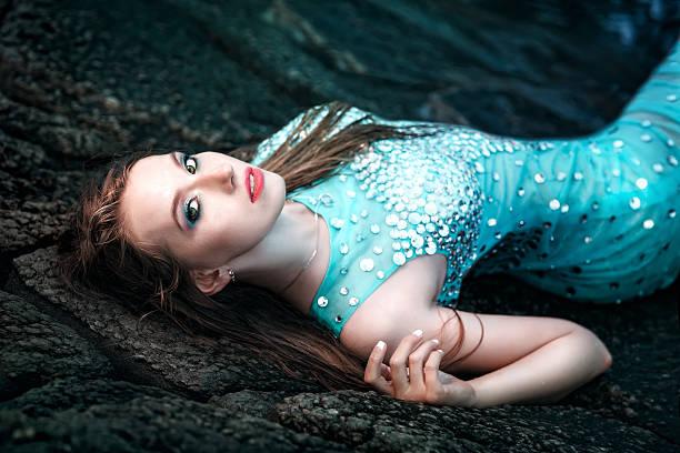 frau posieren am strand mit felsen - meerjungfrau kleid stock-fotos und bilder