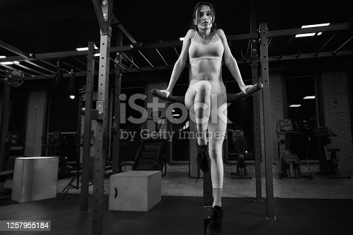 Monochrome full length portrait of athletic woman with perfect body doing triceps dips on parallel bars in gym. Brunette female in light sportswear posing in dark atmosphere and looking at camera.