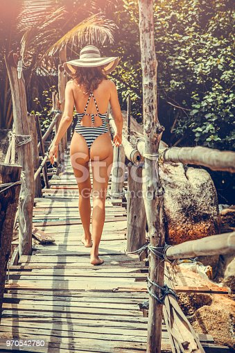 woman in a boho stile posing on the tropical beach