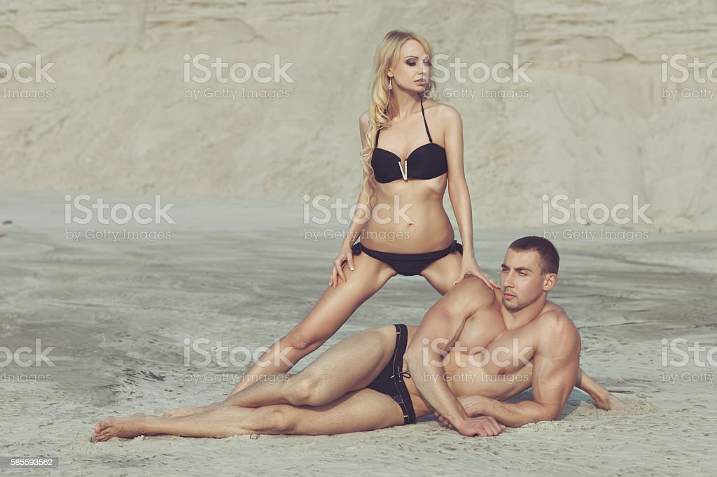 Woman posing with a male bodybuilder on the beach. stock photo