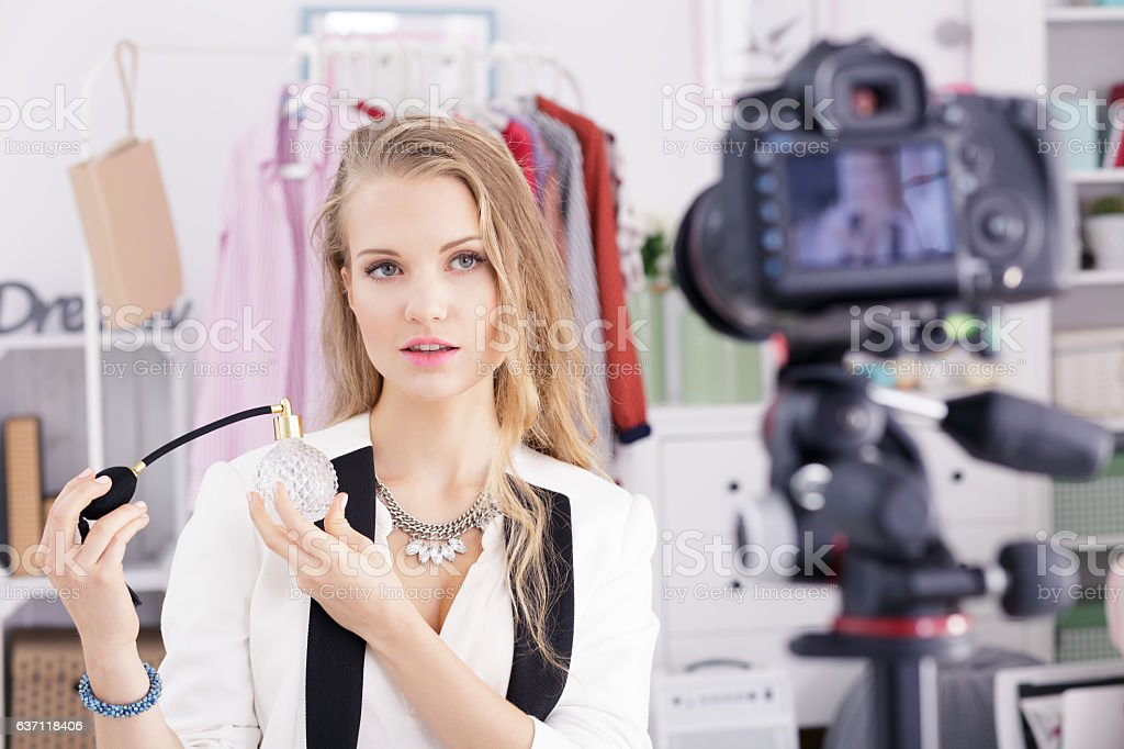 Woman posing with bottle of perfumes stock photo