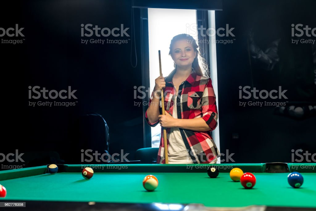 Woman posing with cue in billiard pub - Foto stock royalty-free di Adulto