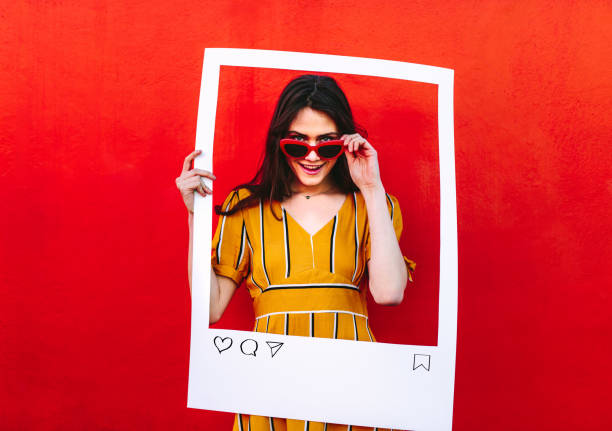 woman posing with social network post photo frame - influencer стоковые фото и изображения