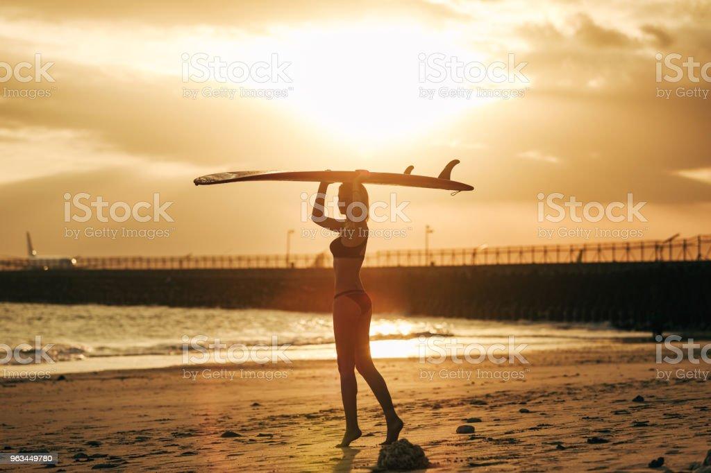 gün batımında resort kafasına surfboard ile poz kadın - Royalty-free Arka Işıklar Stok görsel