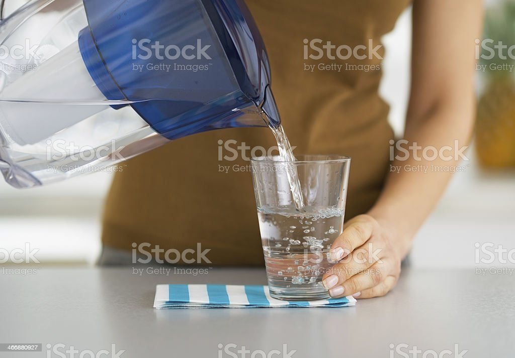 Nahaufnahme der Hausfrau Eingießen von Wasser in Glas - Lizenzfrei Destilliertes Wasser Stock-Foto