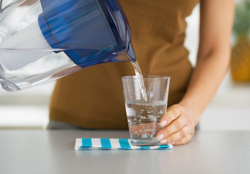 Nahaufnahme Der Hausfrau Eingießen Von Wasser In Glas Stockfoto und mehr Bilder von Destilliertes Wasser