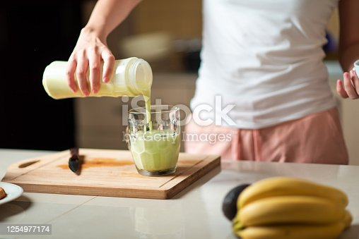 Woman pouring avocado and banana smoothie for a juice with healthy breakfast at home