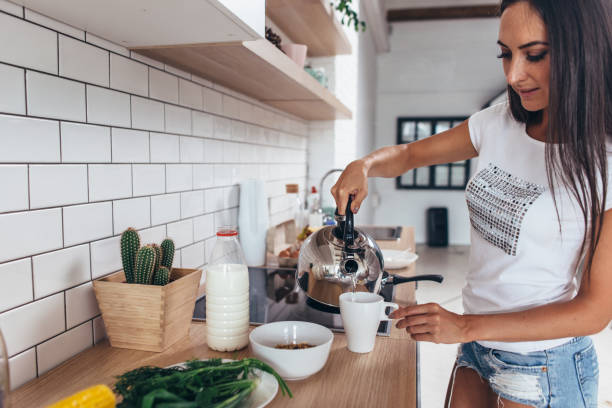 Woman pouring boiling water into a cup from kettle. stock photo