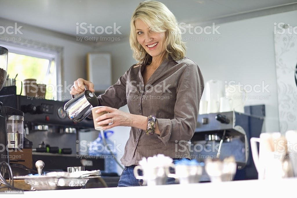 Woman pouring coffee in coffee shop stock photo
