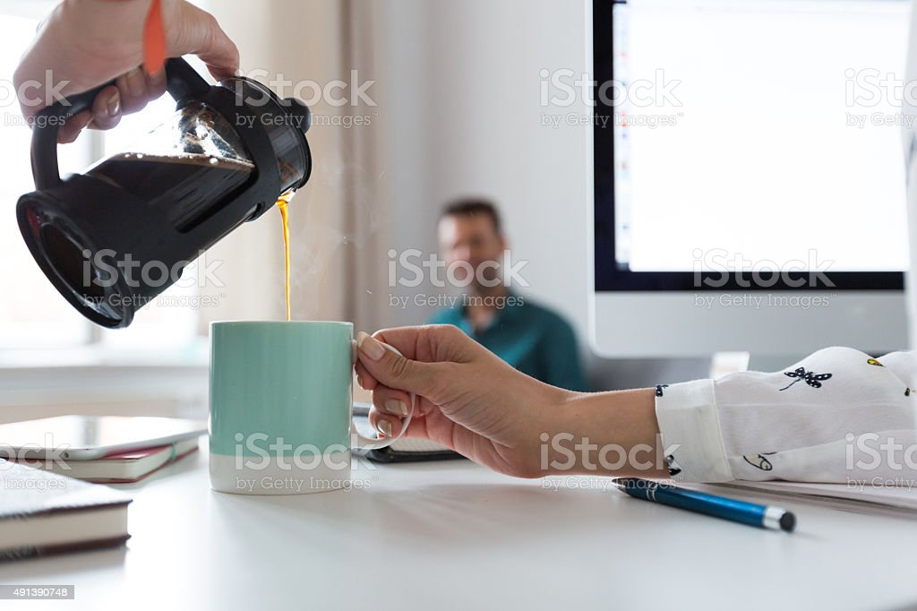 Woman pouring coffee into the cup in an office Woman pouring coffee from french press into the cup in an office. Close up of hands. Defocused man in the background. 2015 Stock Photo