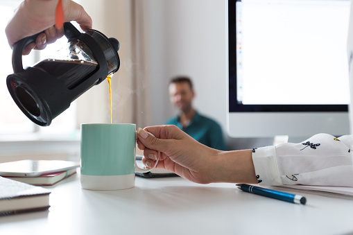 Woman Pouring Coffee Into The Cup In An Office Stock Photo - Download Image Now