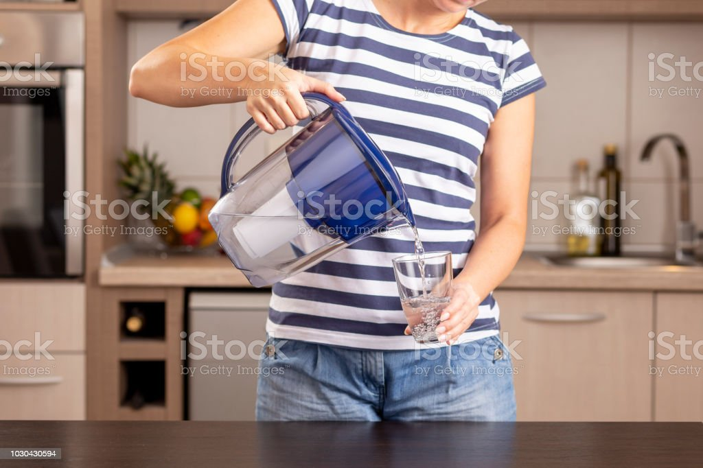 Woman pouring filtered water into a glass stock photo