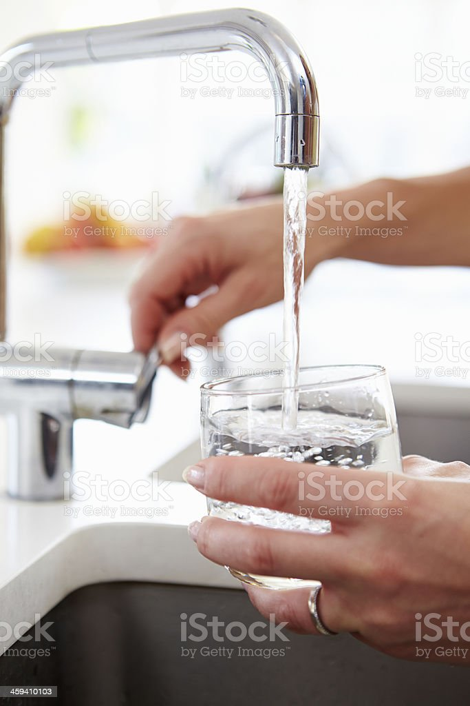Woman Pouring Glass Of Water From Tap In Kitchen stock photo