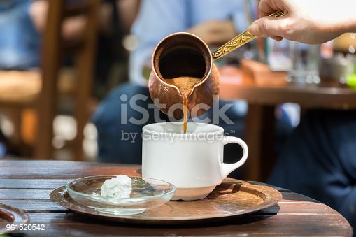 Woman hand pouring greek coffee from a copper pot on a white cup placed on a tray with loukumi