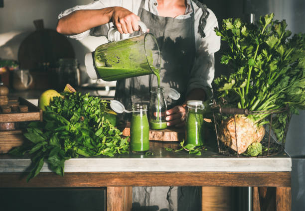 Woman pouring green smoothie from blender to bottle Making green detox take-away smoothie. Woman in linen apron pouring green smoothie drink from blender to bottle surrounded with vegetables and greens. Healthy, weight loss food concept food state stock pictures, royalty-free photos & images