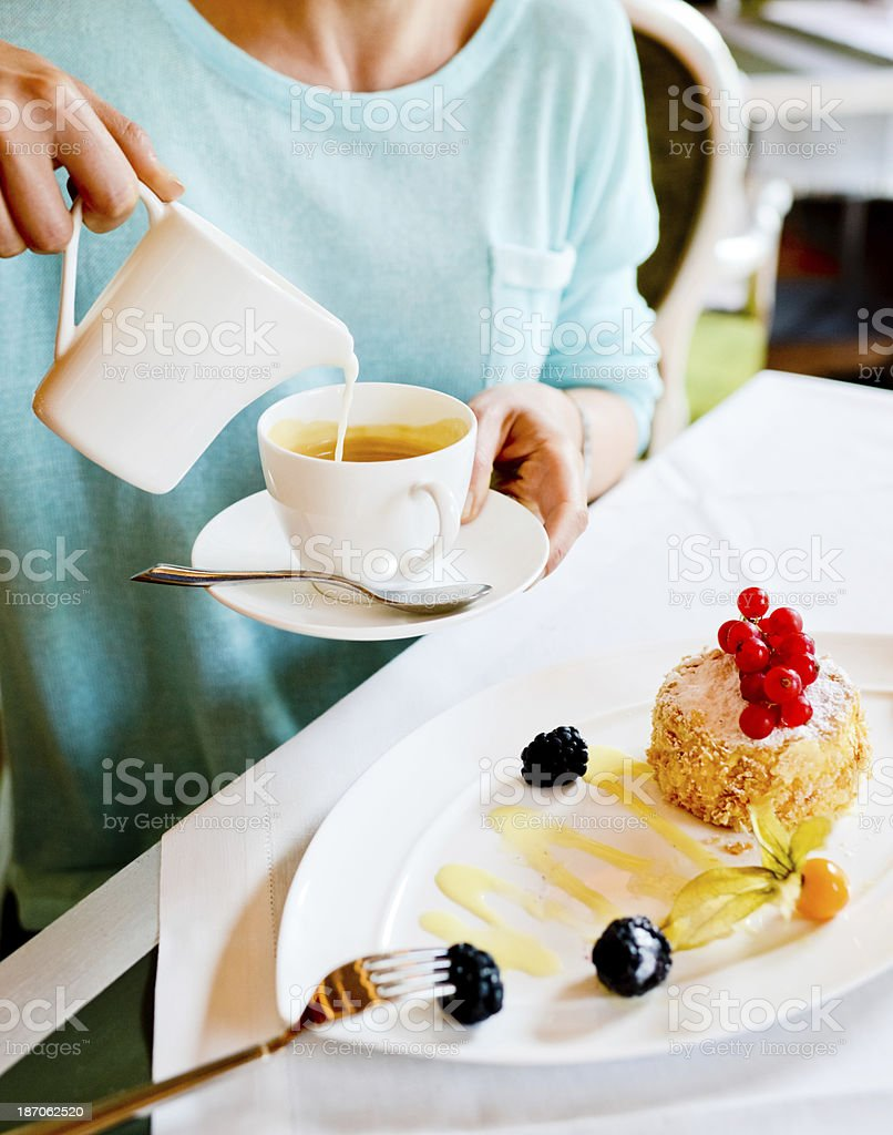 Woman pouring milk in coffee royalty-free stock photo