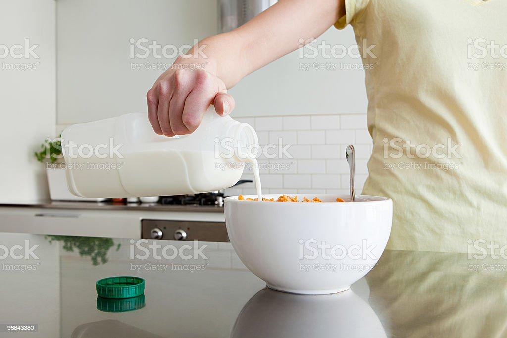 Femme, verser le lait dans les céréales - Photo