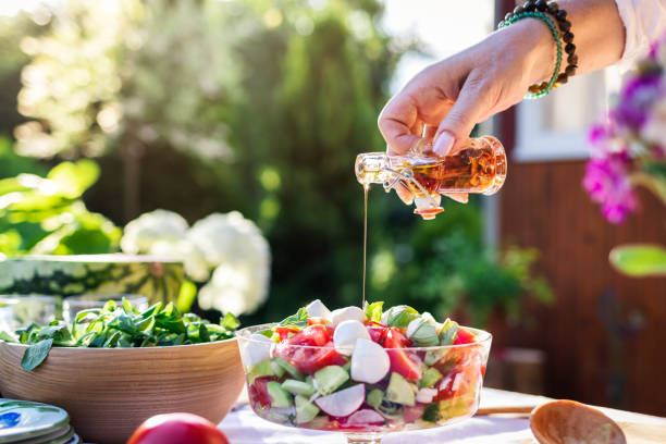 Woman pouring olive oil at salad. Preparing food in garden stock photo
