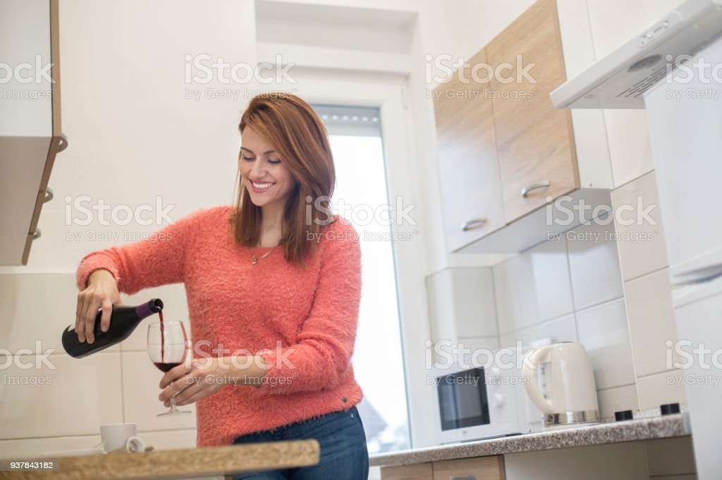 Woman pouring red wine stock photo
