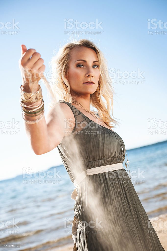 Woman pouring sand outdoors at the beach royalty-free stock photo