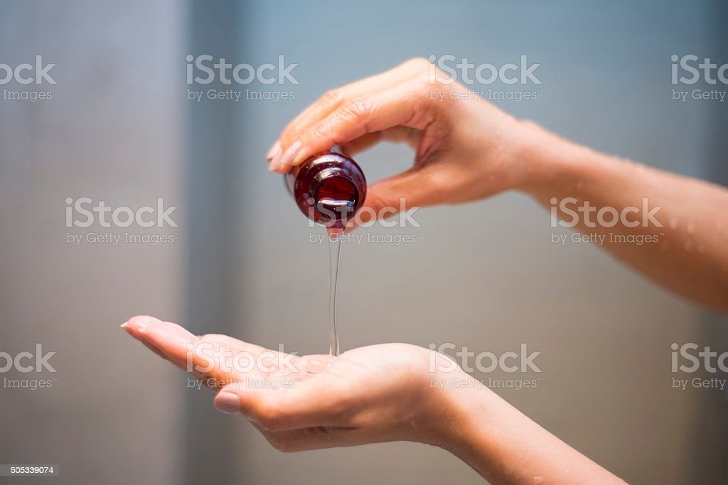 woman pouring shampoo from bottle into hand stock photo