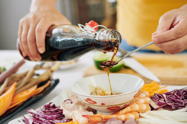 Woman pouring soy sauce into small bowl stock photo
