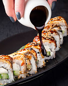 Woman pouring teriyaki sauce on rolls. Black wooden background.