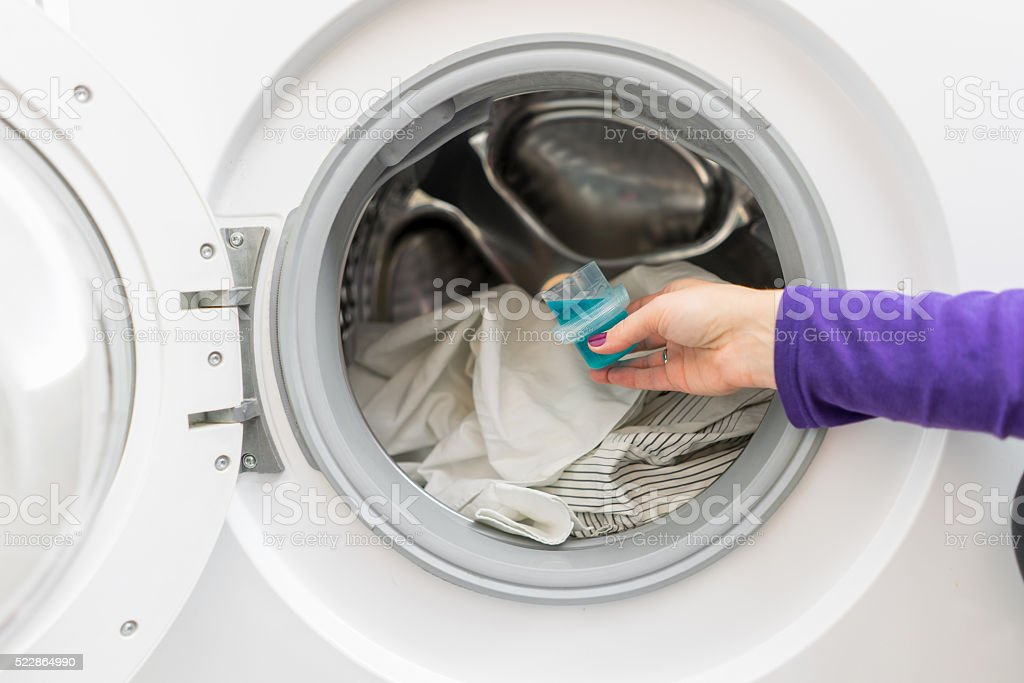 Woman pouring washing liquid, into the washing machine stock photo