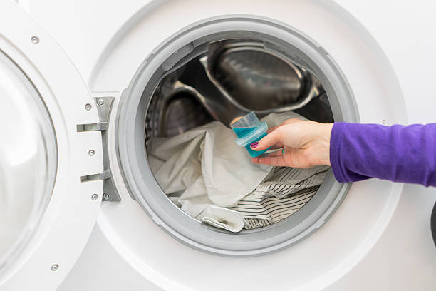 Woman pouring washing liquid, into the washing machine Woman pouring washing liquid, into the washing machine laundry detergent stock pictures, royalty-free photos & images