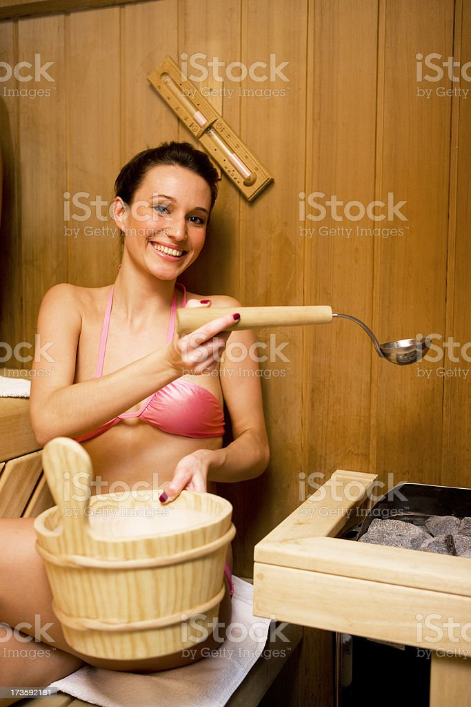 Woman pouring water on rocks in sauna royalty-free stock photo