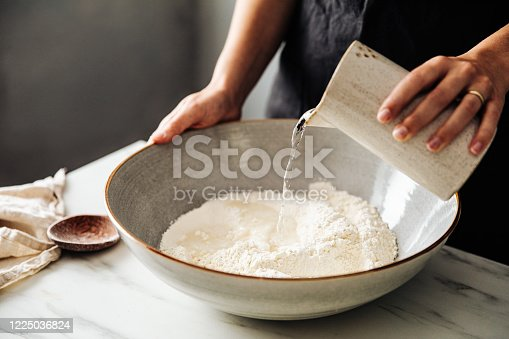istock Woman pouring water on rye and wheat flour in bowl 1225036824