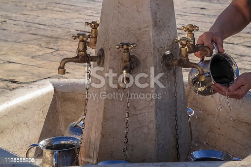 istock Woman pouring water onto her hands to cleanse at Western Wall, Old City Jerusalem, Israel 1128588208