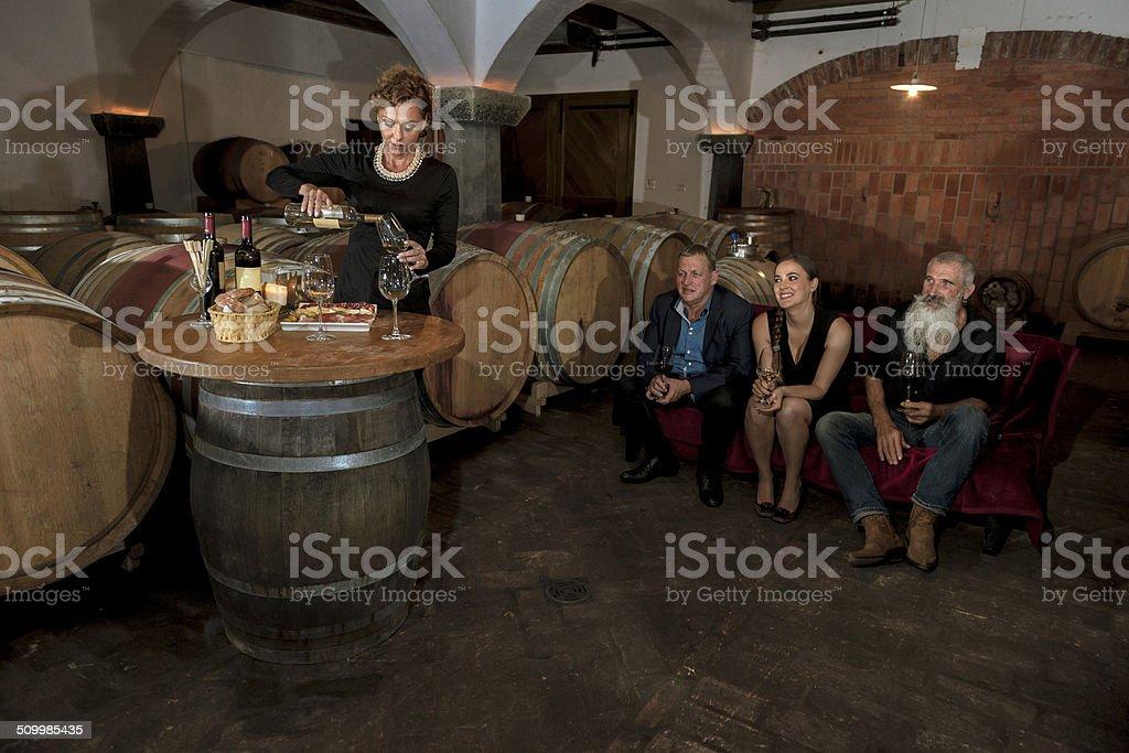 Woman Pouring Wine, Friends Enjoying, Cellar in Europe stock photo
