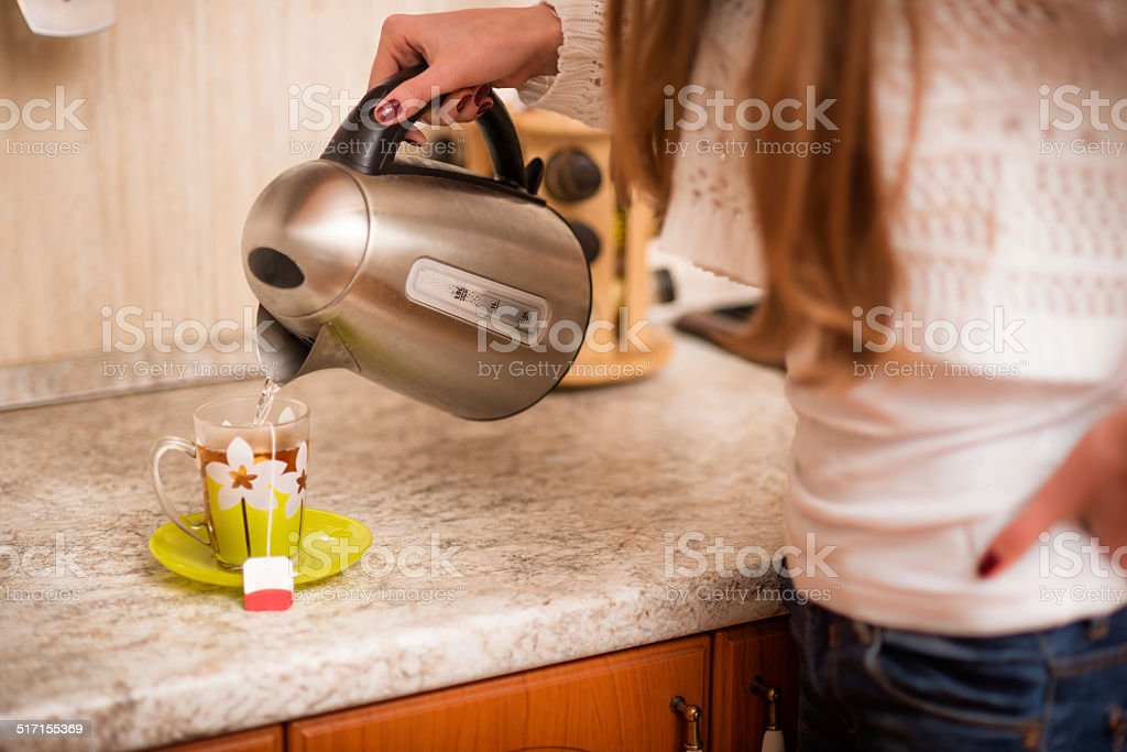 Woman pours boiling water into the cup of tea stock photo