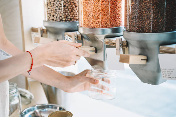 Woman pours red lentils in glass jar from dispensers in zero waste shop. stock photo