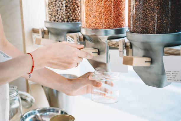 Frau gießt rote Linsen in Glas aus Spendern in Null-Abfall-Shop. – Foto