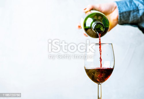 Woman pours red wine into a glass, close-up, selective focus. Free space for text, copy space. Grey background.
