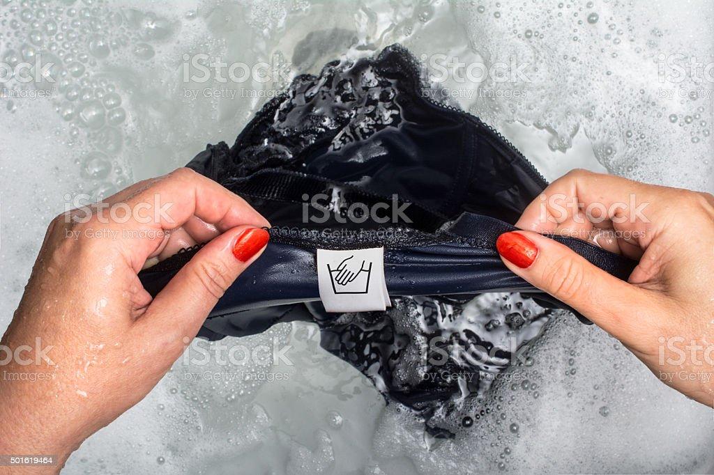 Woman pov reading hardwash label on blue bodysuit stock photo