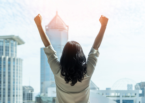 Woman power and girl strength in business achievement, winning and career success with strong businesswoman leader in office raising fists with ambition looking forward to city building background
